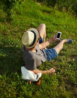 Portret młodego atrakcyjnego nowoczesnego stylowego mężczyzny w dorywczo tkaniny w kapeluszu w okularach siedzi w parku w zielonej trawie oglądając telefon