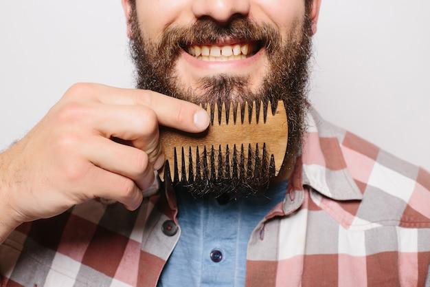 Portret młodego atrakcyjnego rudowłosego mężczyzny hipster z poważnym i pewnym spojrzeniem, trzymając drewniany grzebień i robi jego grubą brodę. stylowy brodaty fryzjer w kraciastej koszuli czesanie w salonie. poziomy