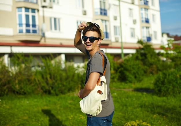 Portret młodego atrakcyjnego uśmiechniętego nowoczesnego stylowego mężczyzny w dorywczo tkaniny w kapeluszu w okularach w parku