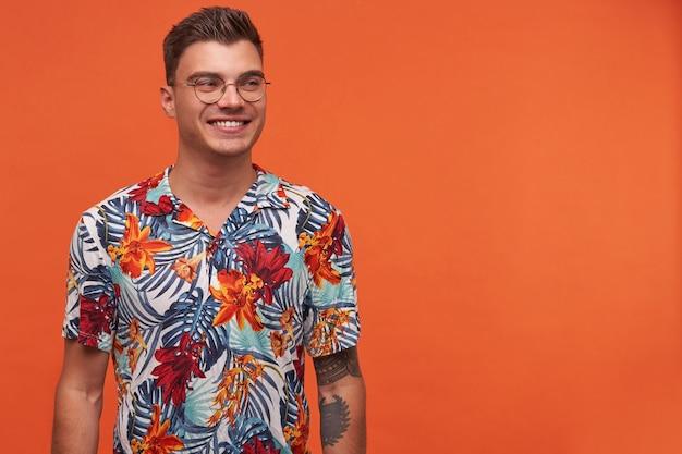 Portret młodego atrakcyjnego wesołego faceta w kwiecistej koszuli, wygląda na szczęśliwego, stoi na pomarańczowym tle z miejsca na kopię i szeroko się uśmiecha.