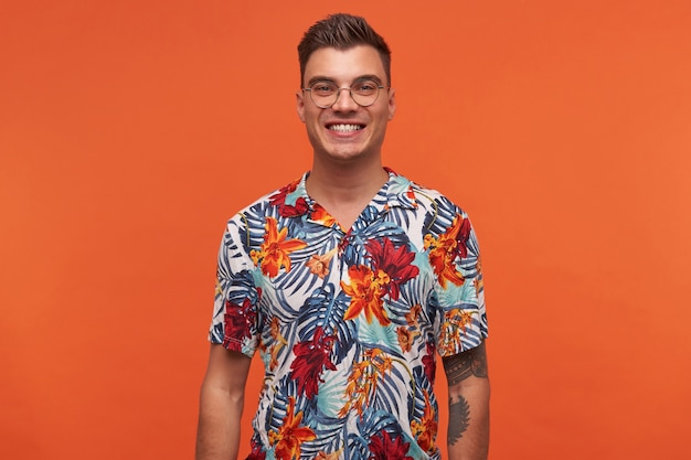 Portret młodego atrakcyjnego wesołego faceta w kwiecistej koszuli, wygląda szczęśliwy, stoi na pomarańczowym tle i szeroko się uśmiecha.