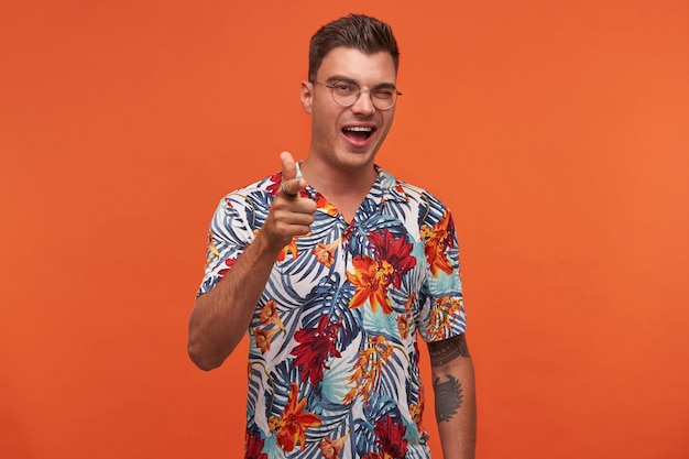 Portret młodego atrakcyjnego wesołego faceta w okularach i kwiecistej koszuli, pokazuje aparat z drobniejszym, stoi na pomarańczowym tle i patrzy w kamerę, mrugnął i szeroko się uśmiechając.