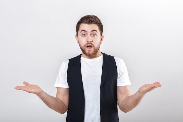 Portret młodego atrakcyjnego zaskoczony mężczyzna brunetka w białej koszuli na szarym tle. zaskakujący fakt