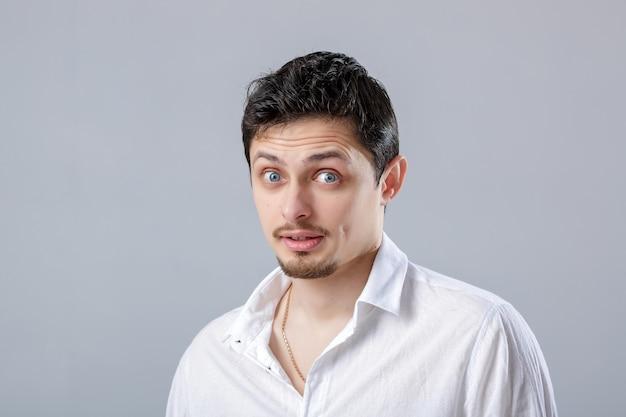 Portret młodego atrakcyjnego zaskoczony mężczyzna brunetka w białej koszuli na szarym tle.