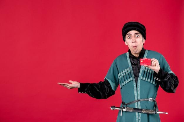Portret młodego azerskiego mężczyzny w tradycyjnym stroju, trzymającego kartę kredytową na czerwono
