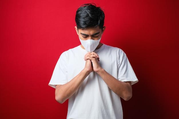 Portret młodego azjaty noszącego maskę ochronną przeciwko koronawirusowi, modlącego się o koronawirusa, szybko zostaje pokonany na czerwonym kolorze