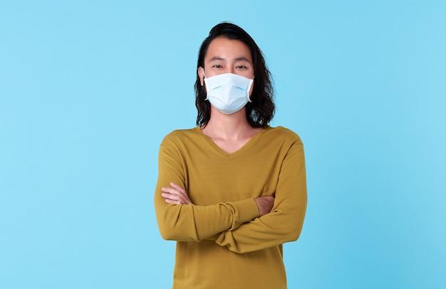 Portret młodego azjatyckiego mężczyzny noszącego maskę chroniącą przed corovavirusem na białym tle na niebieskim tle studia.