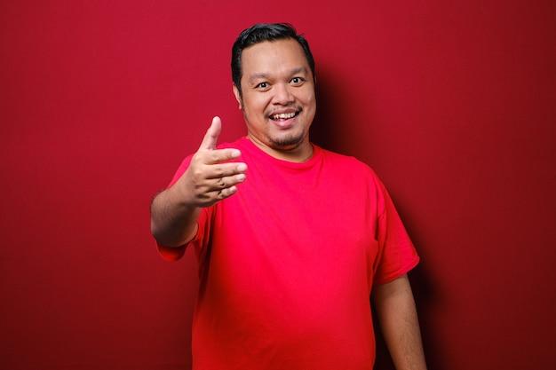 Portret młodego azjatyckiego mężczyzny oferującego uścisk dłoni i uśmiechającego się na czerwonym tle