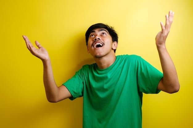 Portret młodego azjatyckiego mężczyzny świętującego zwycięstwo, wygrywającego gestu uśmiechającego się i witającego coś z góry z koncepcją przestrzeni kopii