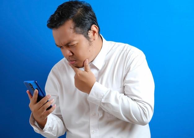 Portret młodego azjatyckiego mężczyzny w dorywczo białej koszuli, próbującego uważnie przeczytać wiadomości na swoim smartfonie, ciekawy wyraz twarzy