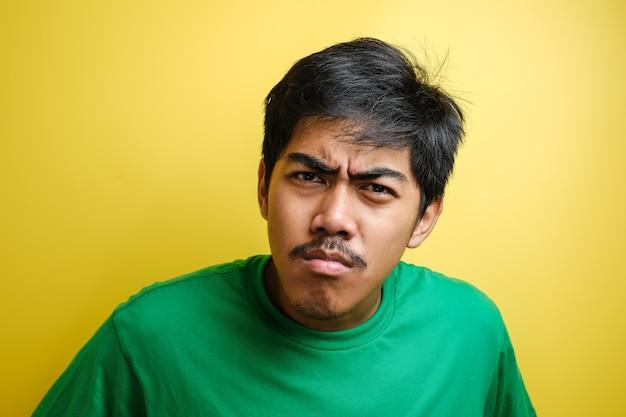 Portret młodego azjatyckiego mężczyzny w swobodnej zielonej koszuli, wpatrującego się w kamerę z podejrzanym cynicznym wyrazem twarzy na żółtym tle