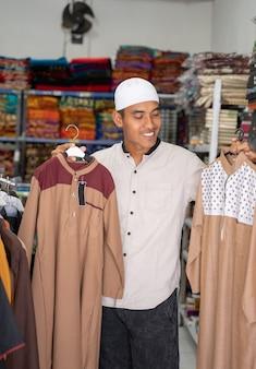 Portret młodego azjatyckiego muzułmanina, który kupuje ubrania w sklepie