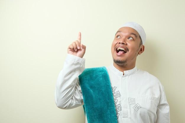 Portret młodego azjatyckiego muzułmanina wyglądał na szczęśliwego, myśląc i patrząc w górę, mając dobry pomysł