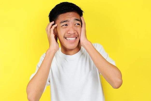 Portret młodego azjatyckiego nastolatka nieszczęśliwego przestraszonego mężczyzny, odizolowanego na żółtym tle