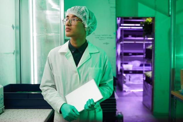 Portret młodego azjatyckiego pracownika noszącego odzież ochronną w pasie stojącego w laboratorium bio oświetlonym zielonym światłem, kopia przestrzeń