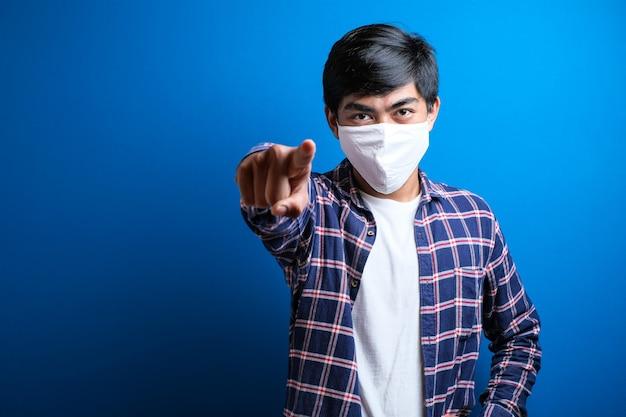 Portret młodego azjatyckiego studenta noszącego flanelową koszulę i maskę skierowaną do przodu, patrząc na kamerę wybierającą kogoś do noszenia maski na niebieskim tle.