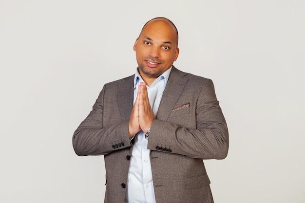 Portret młodego biznesmena african american facet uśmiechnięty, dłonie razem przed nim, trzymając ręce w geście modlitwy, prosząc o przebaczenie za błąd.