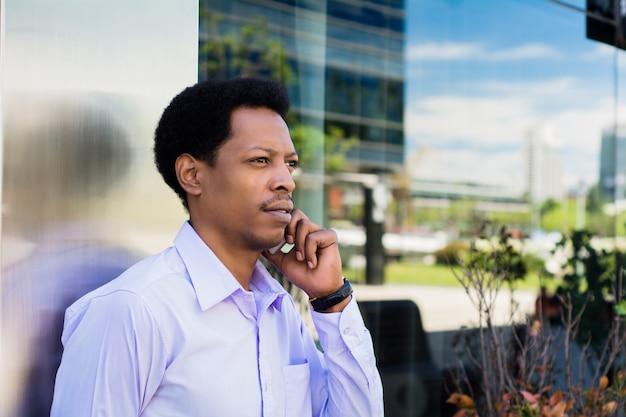Portret młodego biznesmena afro rozmawia przez telefon komórkowy na zewnątrz na ulicy. pomysł na biznes.