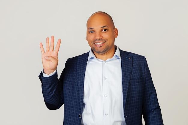 Portret młodego biznesmena afroamerykanów, odnoszącego sukcesy faceta, pokazując palcami numer cztery, uśmiechnięty, pewny siebie i szczęśliwy. mężczyzna pokazuje cztery palce. numer 4.
