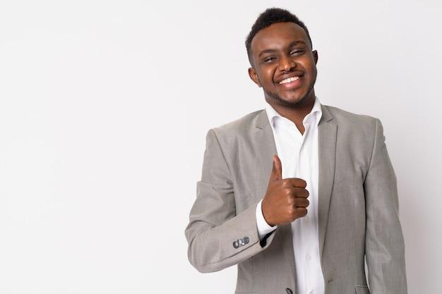 Portret młodego biznesmena afrykańskiego ubrany w garnitur przed białą ścianą
