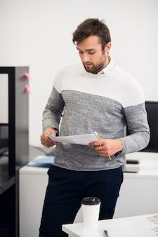 Portret młodego biznesmena analizować jakiś dokument w swoim biurze