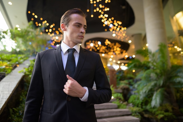 Portret młodego biznesmena chodzenia po schodach podczas myślenia