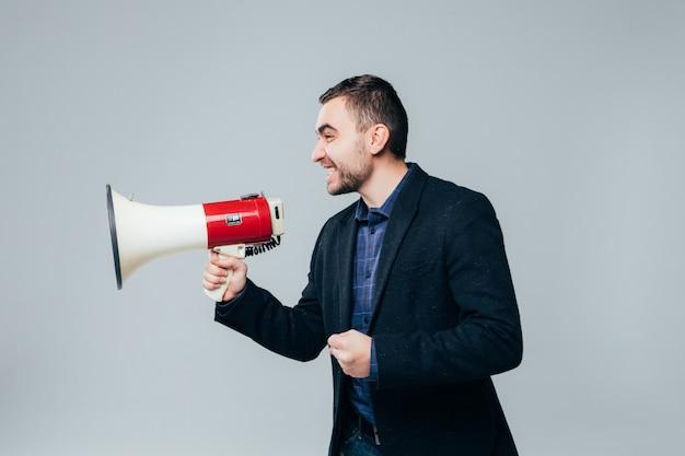 Portret młodego biznesmena krzycząc z megafonem na białym tle