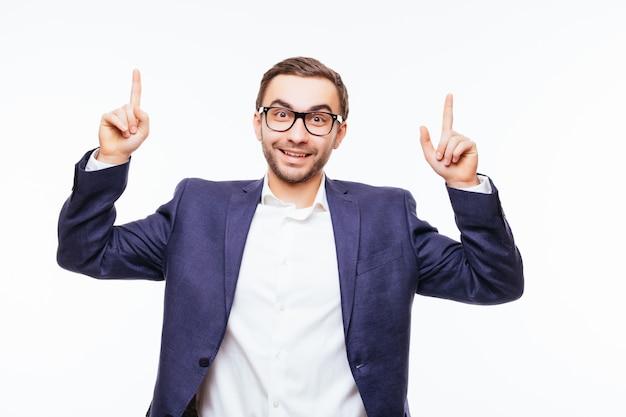 Portret młodego biznesmena mającego pomysł i wskazującego palcem na białym tle na białej ścianie