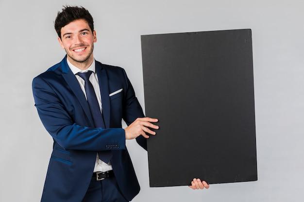 Portret młodego biznesmena mienia pusty czarny plakat przeciw popielatemu tłu