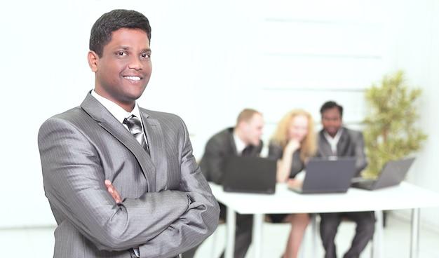 Portret młodego biznesmena na tle biura.