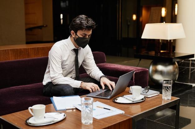 Portret młodego biznesmena noszącego maskę podczas pracy w holu hotelu, kopia przestrzeń