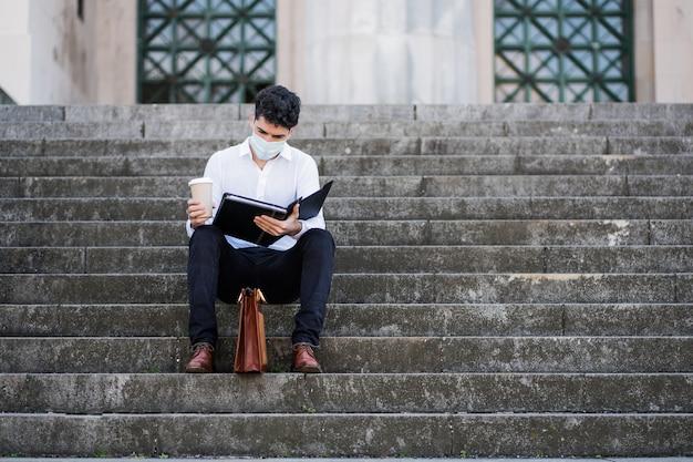 Portret młodego biznesmena noszenia maski i czytania plików siedząc na schodach na zewnątrz. pomysł na biznes