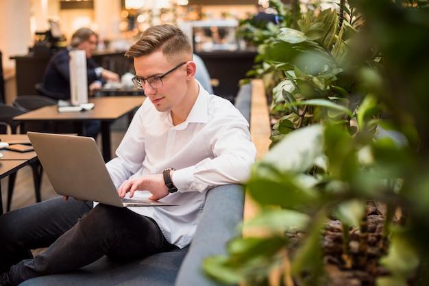 Portret młodego biznesmena obsiadanie na kanapie używać laptop