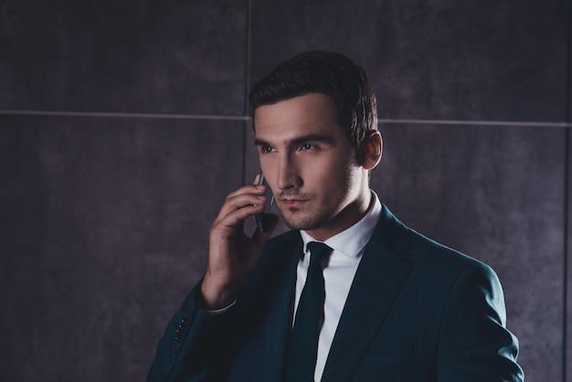 Portret młodego biznesmena, odnoszącego sukcesy, rozmawia przez telefon komórkowy