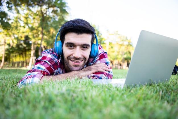 Portret młodego biznesmena przystojny mężczyzna nosi słuchawki i słucha muzyki pop w pobliżu laptopa ma promienny uśmiech i szczęście pomysły na pracę na zewnątrz i relaks w ogrodzie