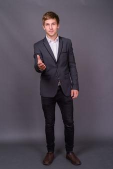 Portret młodego biznesmena przystojny przeciw szarej ścianie