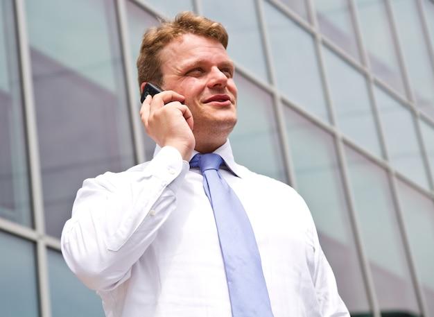 Portret młodego biznesmena rozmawia przez telefon