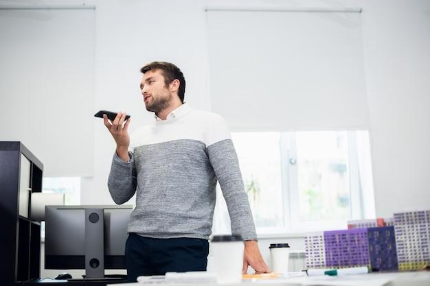 Portret młodego biznesmena rozmawiającego z kimś za pomocą trybu głośników w swoim telefonie