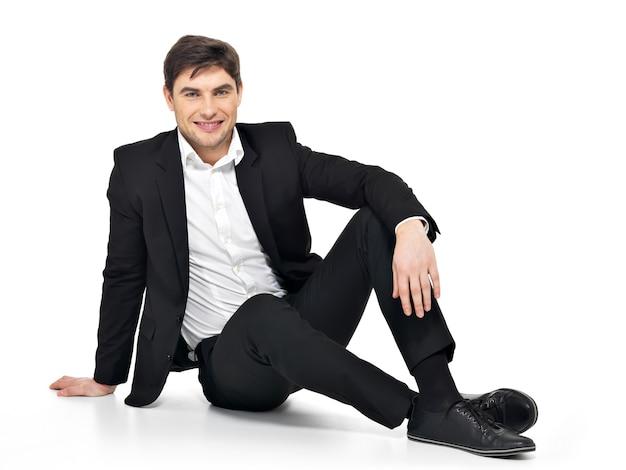 Portret młodego biznesmena szczęśliwy siedzi na podłodze na białym tle.