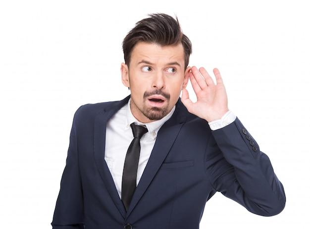 Portret młodego biznesmena trzyma rękę do ucha.