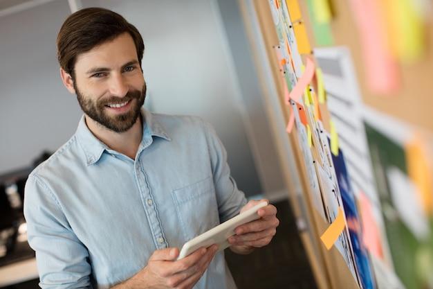 Portret młodego biznesmena, trzymając cyfrowy tablet przez miękką deskę