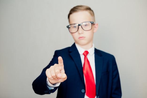 Portret młodego biznesmena w duże okulary i stylowy garnitur. rysuje na szkle, selektywna ostrość