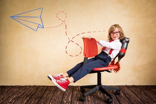 Portret młodego biznesmena z jet packiem jeżdżącym na krześle biurowym