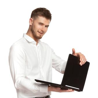 Portret młodego biznesmena z laptopem w ręku w białej koszuli na białym tle na białym tle.
