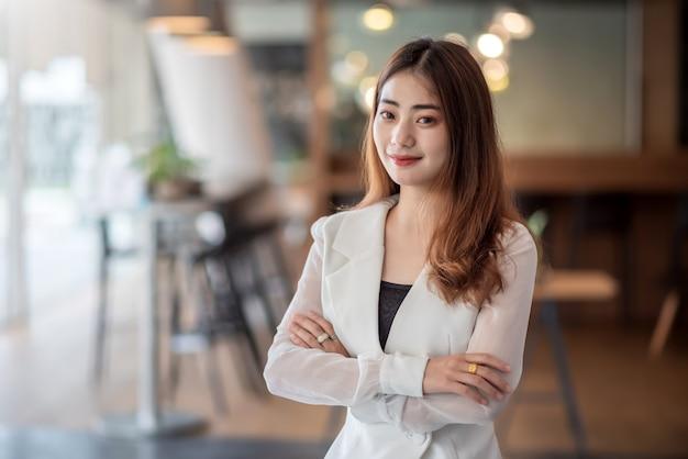 Portret młodego bizneswoman azjatyckiego stojącego w biurze. spójrz na aparat.