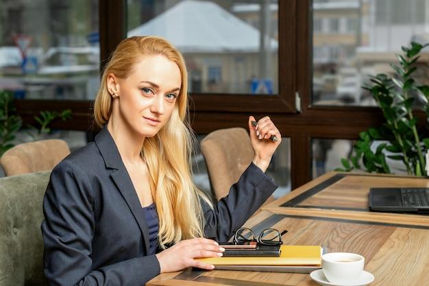 Portret młodego bizneswoman kaukaski z dokumentami i laptopem przy stole patrząc w kamerę w kawiarni
