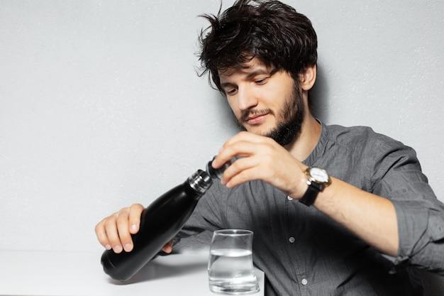 Portret młodego brodacza z rozczochranymi włosami, trzymając stalową butelkę termiczną w pobliżu szklanki wody