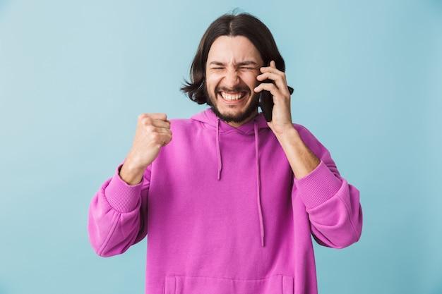 Portret młodego brodatego bruneta w bluzie z kapturem, stojącego na białym tle nad niebieską ścianą, rozmawiającego przez telefon komórkowy, świętującego