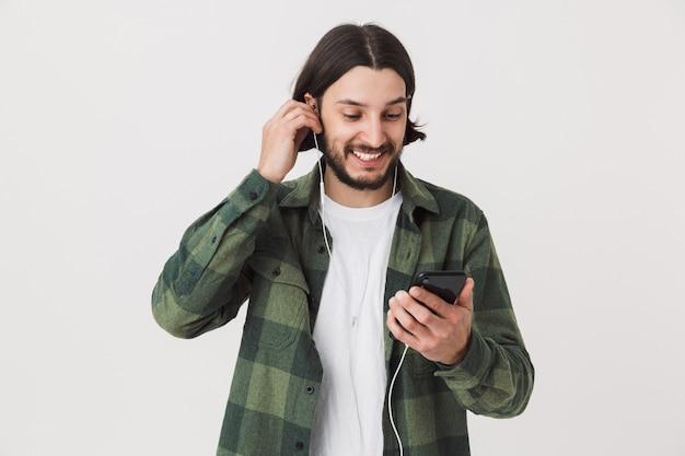 Portret młodego brodatego brunetki noszącego koszulę w kratę stojącego na białym tle nad białą ścianą, słuchającego muzyki przez słuchawki, trzymającego telefon komórkowy