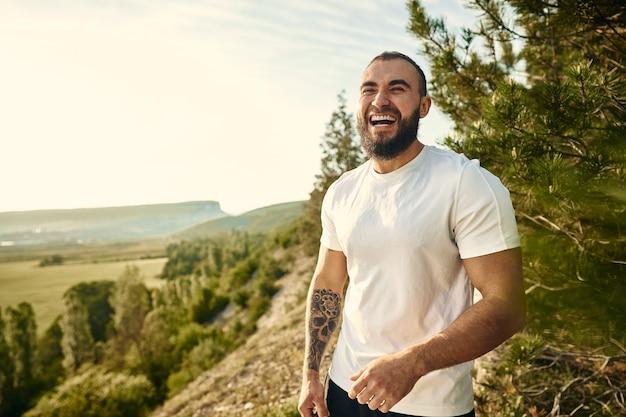 Portret młodego brodatego mężczyzny na zewnątrz w górach